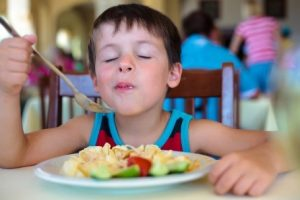 A boy savoring a mouthful of food.