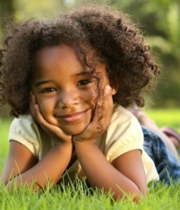 a little girl smiling in the grass.