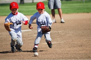 two boys playing baseball, running after a ball.
