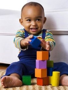 a toddler building blocks and smiling