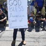 """a person with a sign that says """"God bless America, Land of Immigrants"""""""