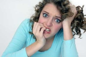 a woman with curly hair in a blue shirt biting her nails and looking distressed.