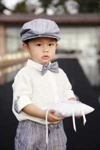 ring bearer holding pillow with ring on it