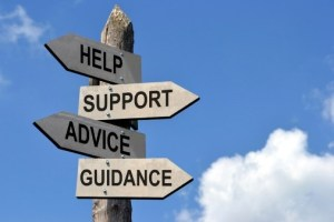 a sign pointing two separate directions with four signs pointing various directions stating: help, support, advice, guidance