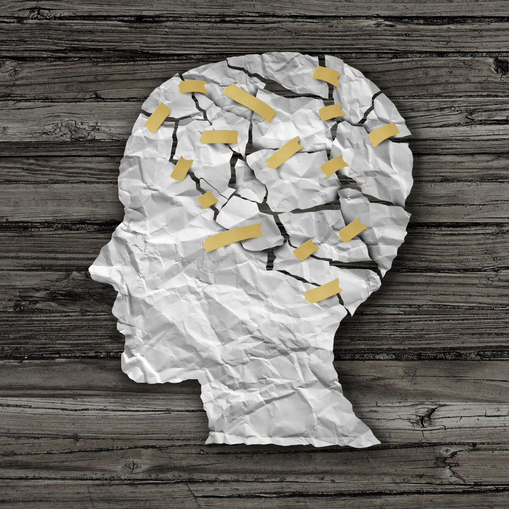 Brain therapy and mental health treatment concept as a sheet of torn crumpled white paper taped together shaped as a side profile of a human face