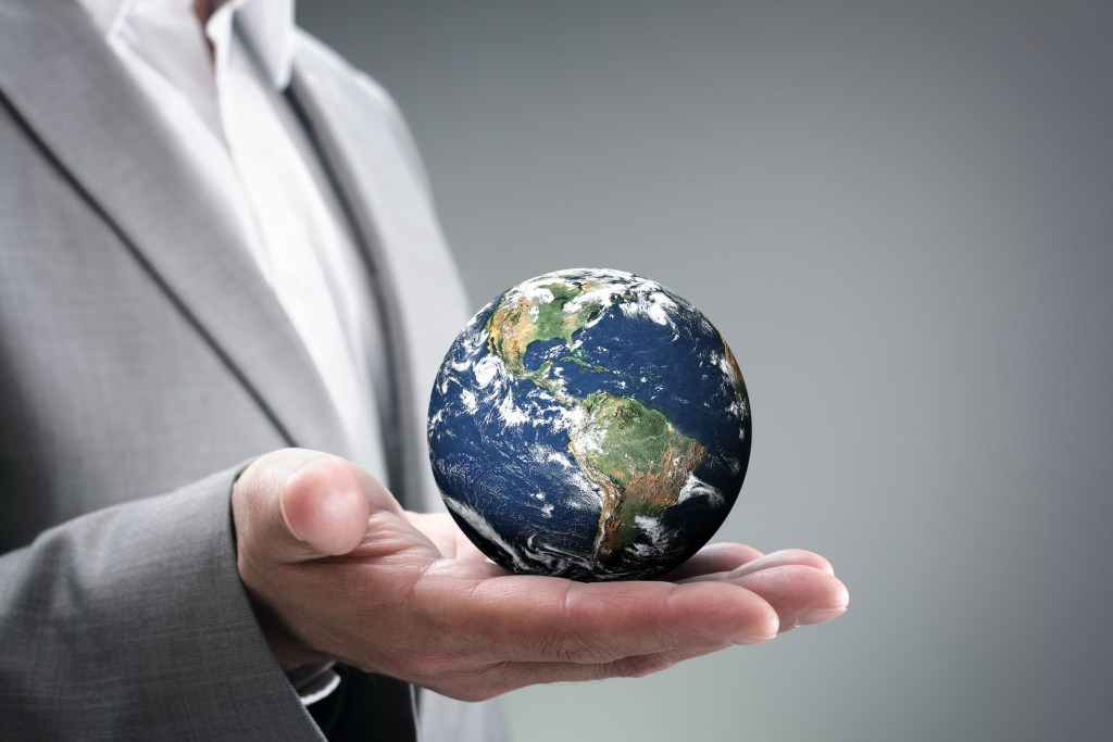 Businessman holding the world in hands concept for global business, communications, politics or environmental conservation Earth