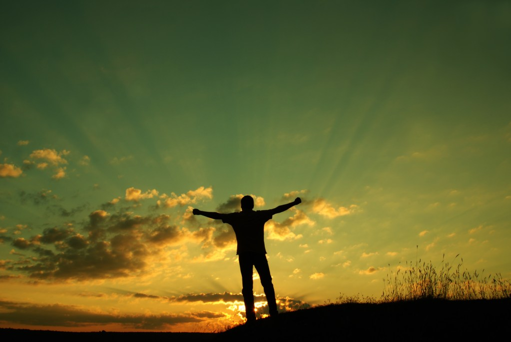 man silhouetted against sunset with his arms outstretched
