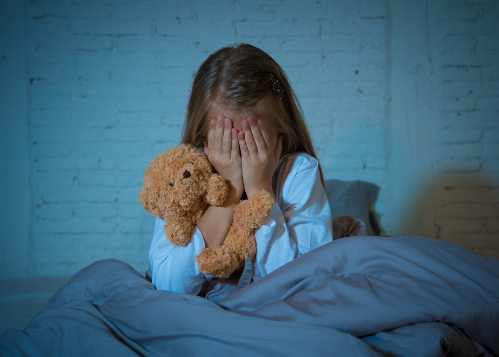 Scared little girl sitting in bed traumatized and in fear, nightmares and psychological distress concept.