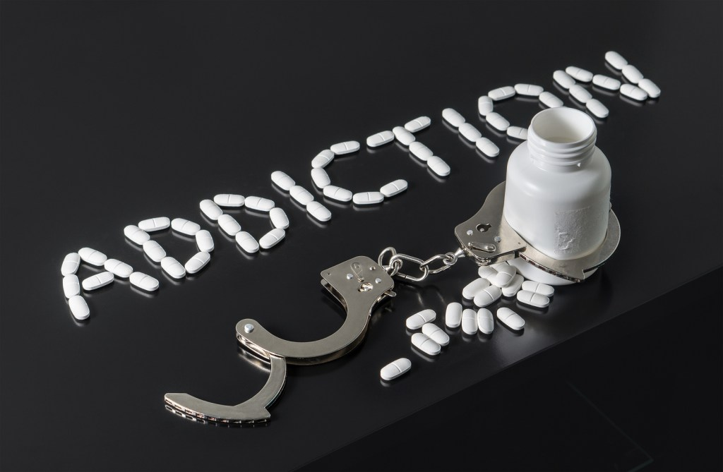 Addiction written with pills. Medicine spilling out from a bottle locked with open handcuffs.