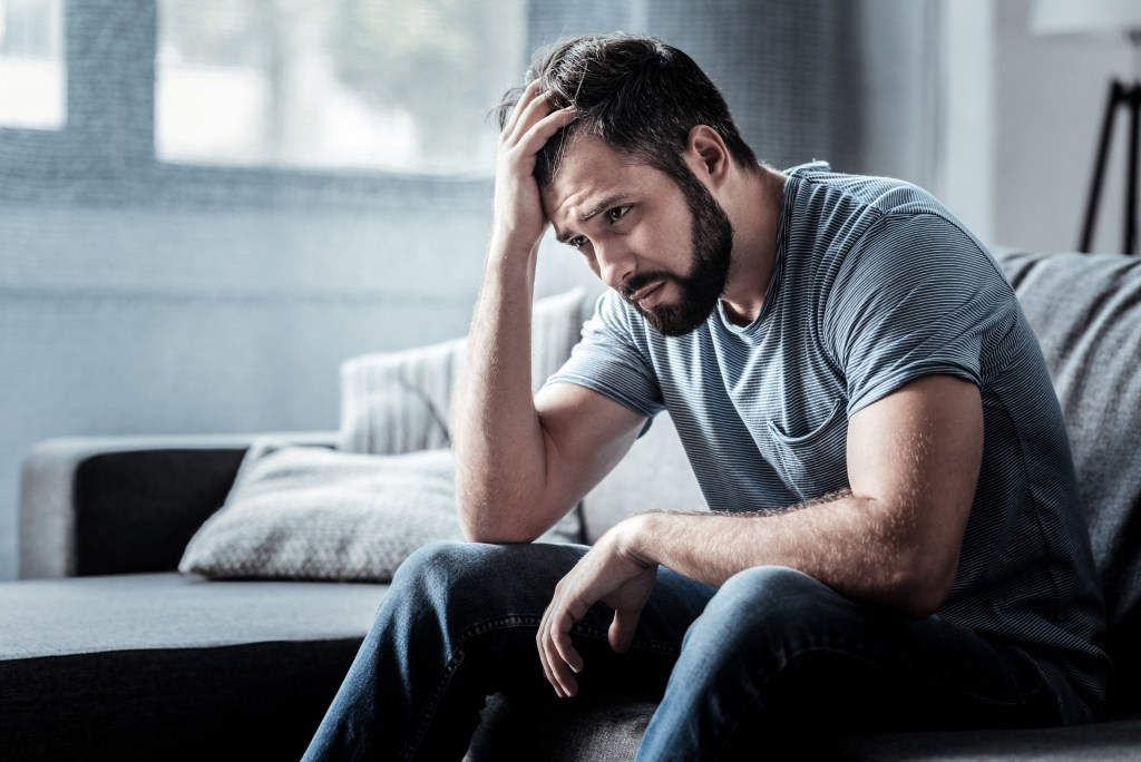 depressed young man with head in his hand, worried, depressed