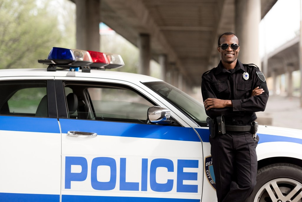 African police officer with crossed arms leaning back on car