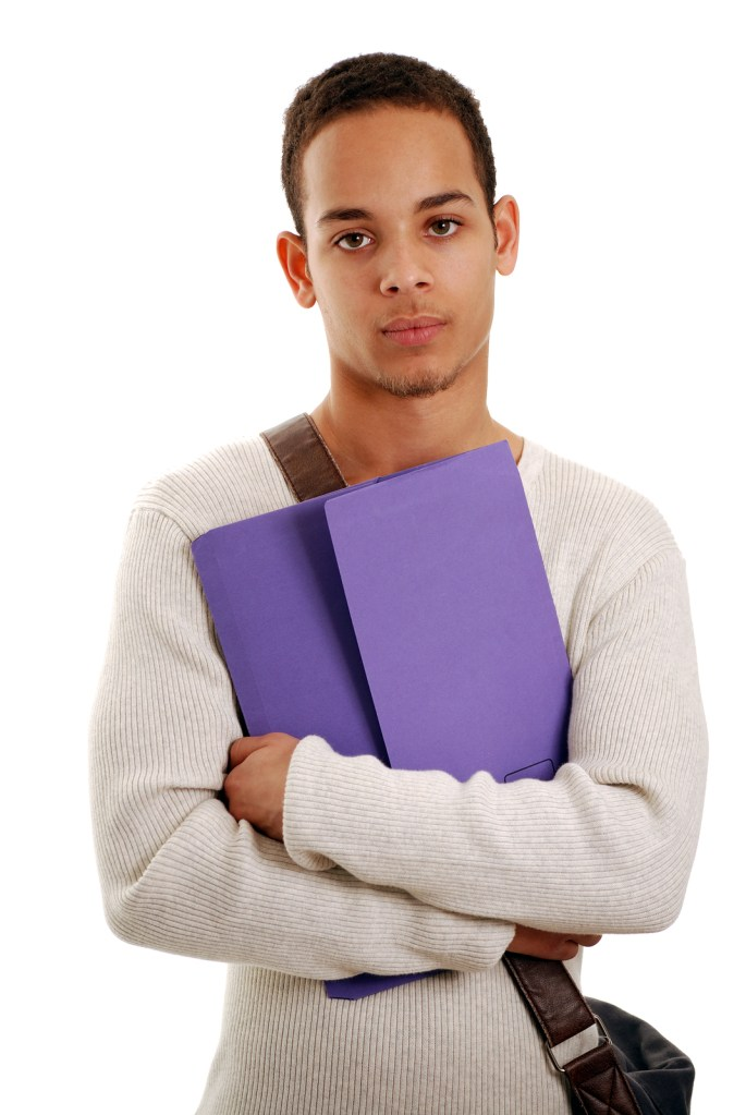Young African American male teen holding notebook and school bag