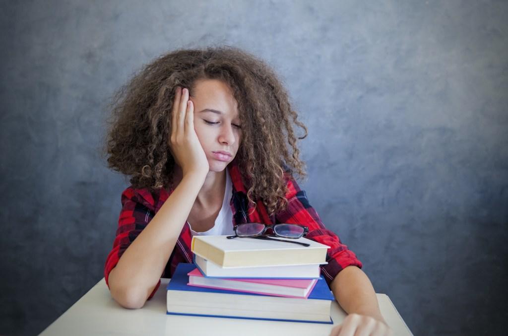 Sleepy teen girl resting on her stack of books.