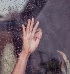 Sad woman with hand up at window with rain drops.