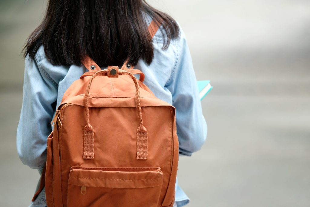 Back of student girl holding books and carry school bag while walking in school campus background