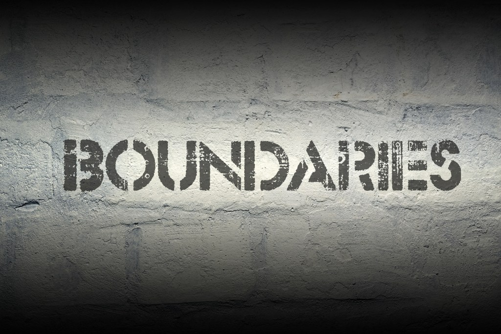 boundaries stencil print on the grunge white brick wall