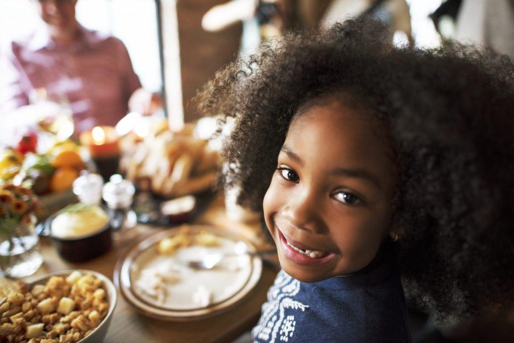 Little Kid Smiling at dinner table
