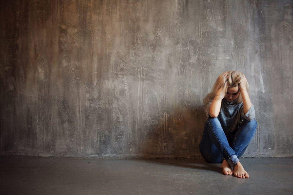 Depressing girl sitting on the floor.