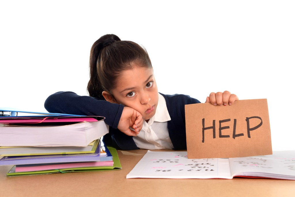 """girl with books at desk holding sign """"help"""" with her reading, homework"""