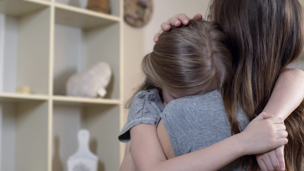Woman comforting and hugging her upset sad daughter