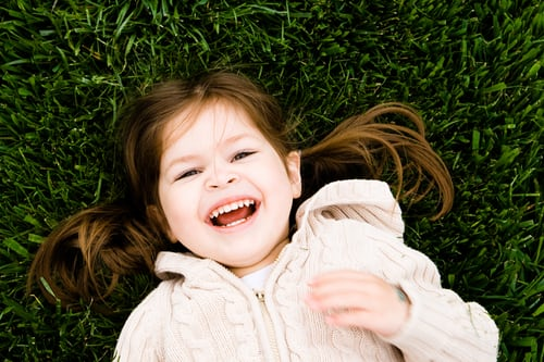 Little girl laying in the grass smiling!