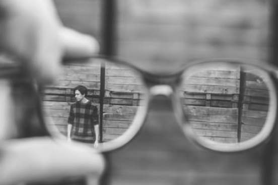 Looking at a person through close up eyeglasses, blurry background