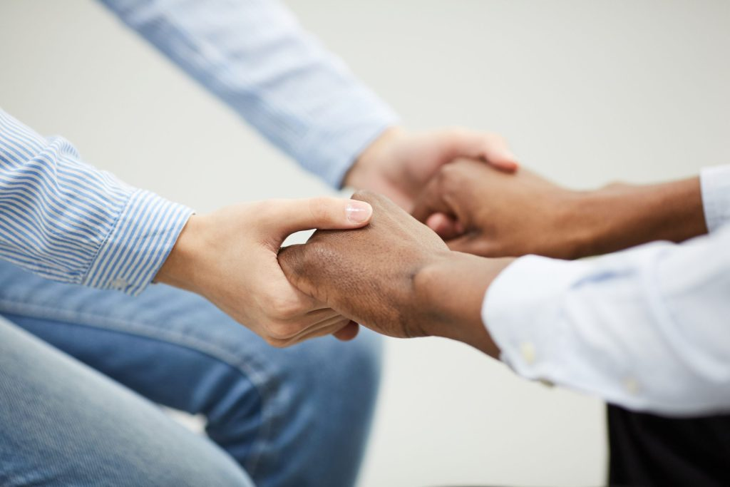 two people holding hands heartily, showing support