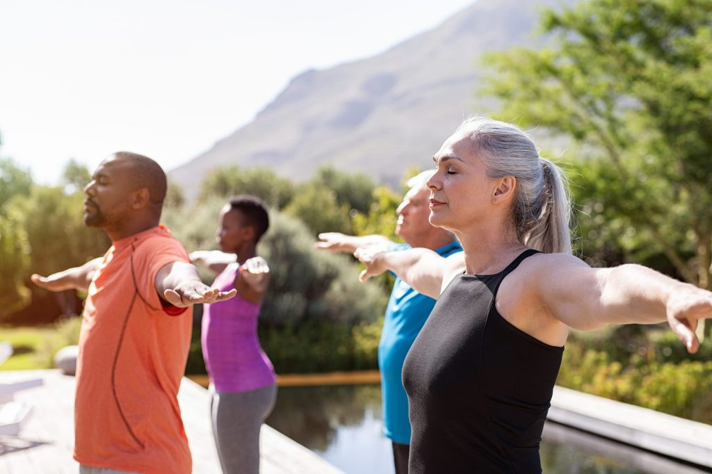 Mature yoga class doing breathing exercise.
