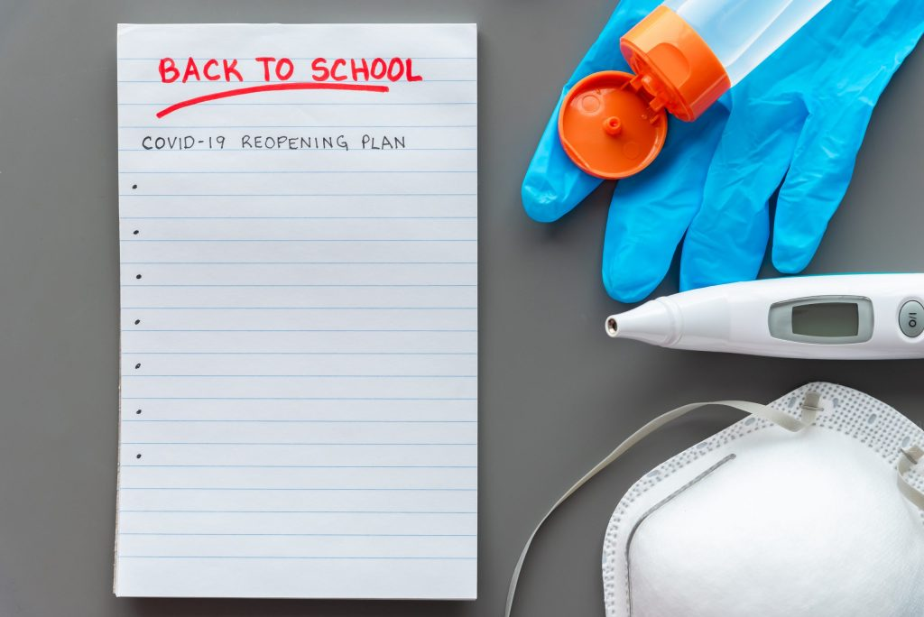 COVID-19 back to school reopening plan concept shot. Note pad with medical mask, surgical glove, digital thermometer and hand sanitizer