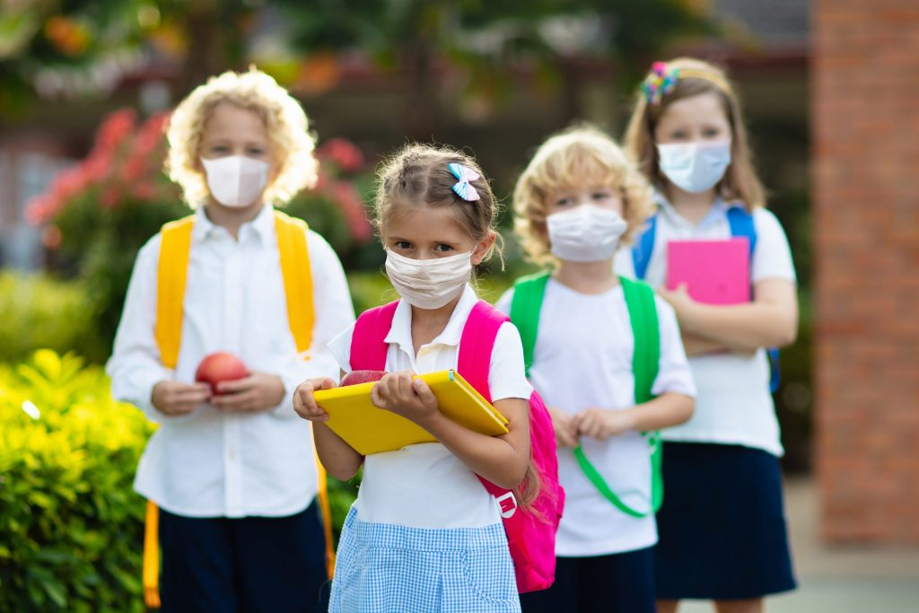 School children wearing face mask during corona outbreak, after covid-19 quarantine and lockdown. Group of kids in masks for coronavirus prevention.