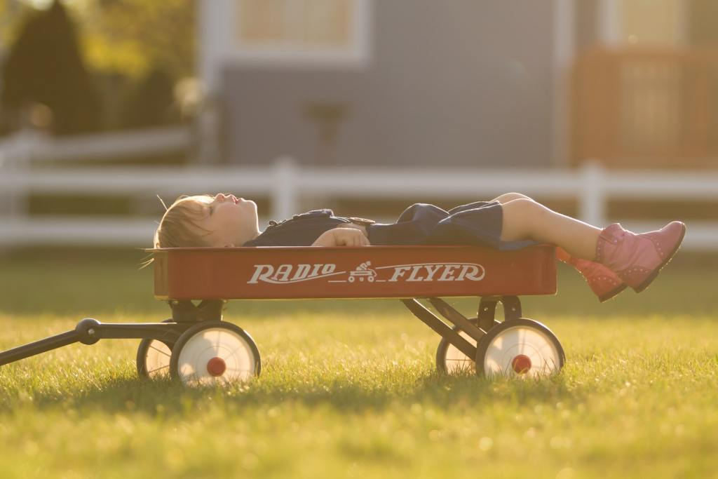 Little kid daydreaming in a wagon
