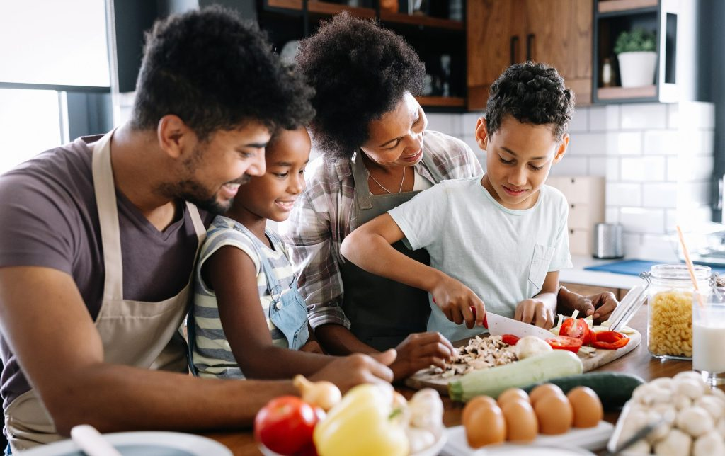 Black family in the kitchen cooking healthy food together at home.