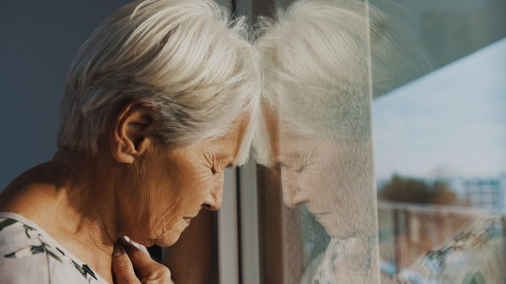 hopeless elderly woman, feeling loneliness during the lockdown.