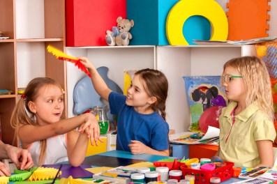 School children with scissors in kids hands cutting paper in class room.