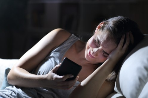 Sad girl upset over text on smart phone at night at home