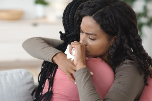 Closeup of crying black woman hugging and supporting her upset friend