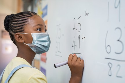 African American girl wearing face mask and writing solution of sums on white board at school during Covid.