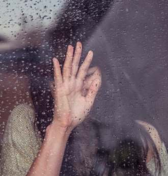 Woman desperate with her hands up to rain-splashed window crying
