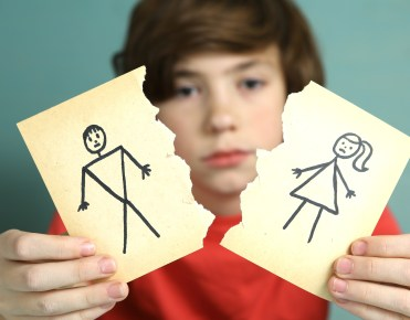 sad preteen boy unhappy about parents divorce hold man and woman paper drawing torn apart