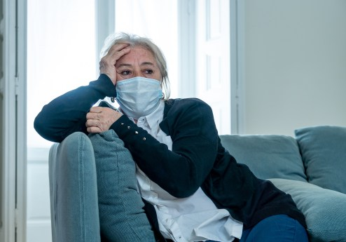 Lonely depressed woman with protective mask isolated at home, sad and worried lockdown, social distancing and Mental health.