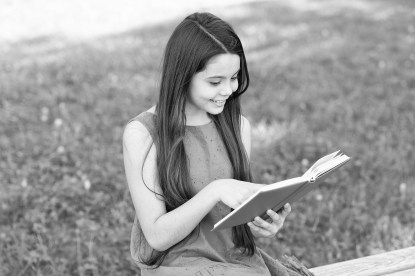 girl read book on park bench, summer outdoors.