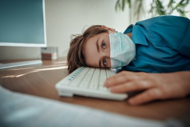Coronavirus and life. Boy schoolboy student in a medical mask stays home at distance learning due to quarantine because of COVID-19.