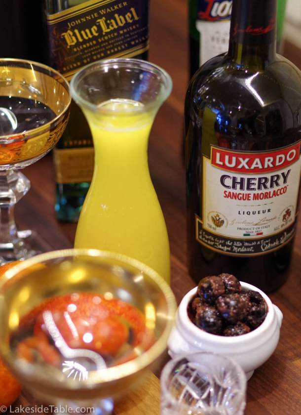 decomposed ingredients for a blood and sand cocktail: cherries, blood orange juice, scotch and luxardo liqueur