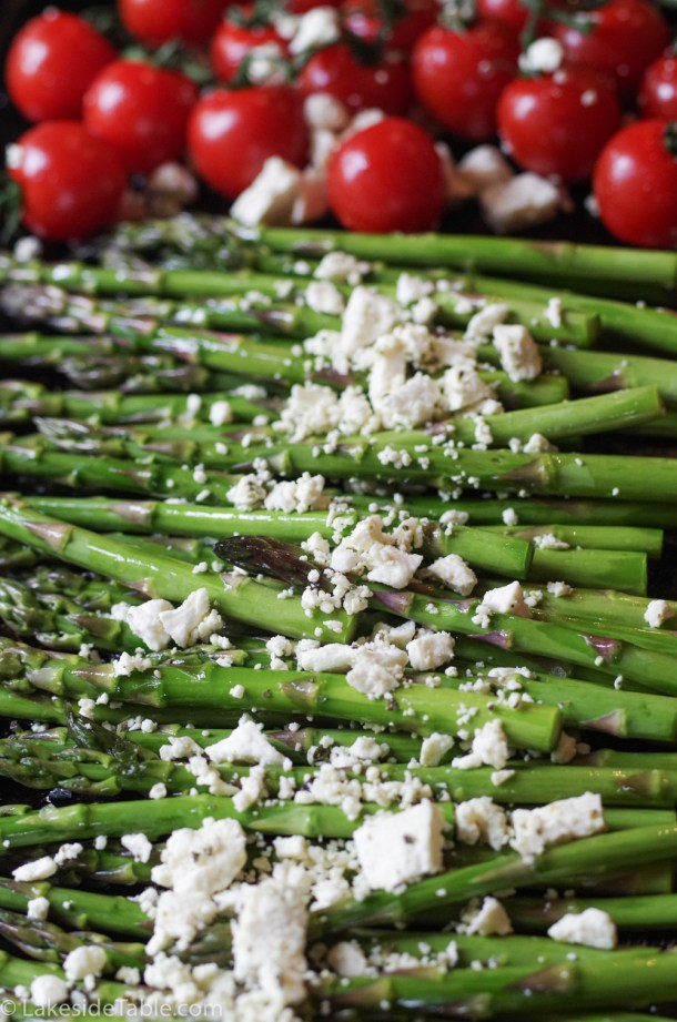 Braised Asparagus - Bright green asparagus laid out on a baking sheet with white feta sprinkled on top in front of bright red cherry tomatoes