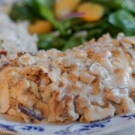 chicken breast smothered in morel mushroom sauce with rice and spinach salad on a plate