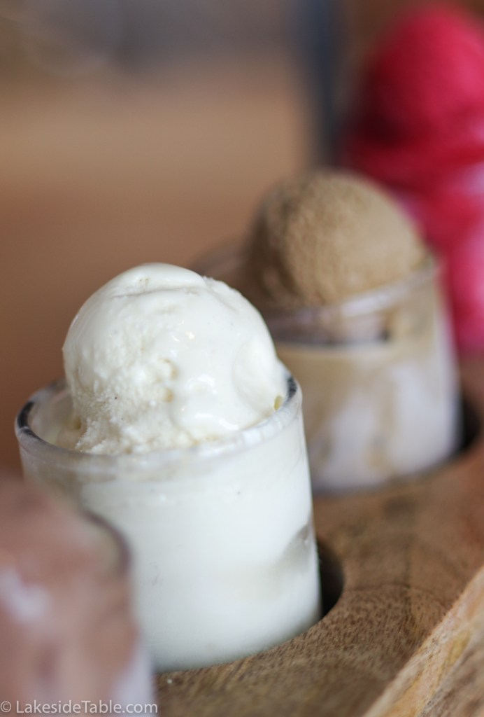 5 ice cream flavors lined up in separate cups on a board on a wooden table