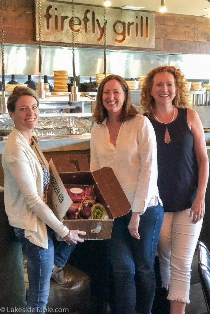Three women smiling in a restaurant holding a box of produce from LEAF Little Egypt Alliance of Farmers