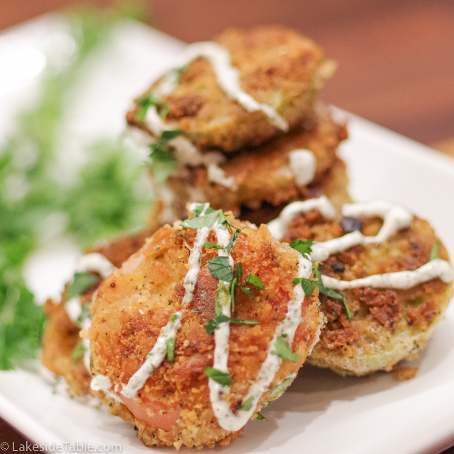 A stack of fried green tomatoes golden brown and crispy with herb mayo on a white plate