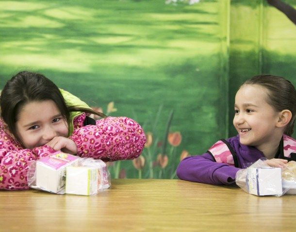 2 young girls with school lunches