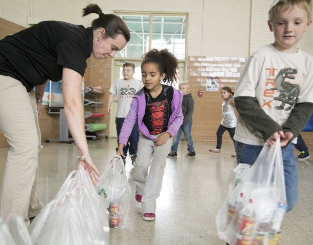 teacher helping kids bag food